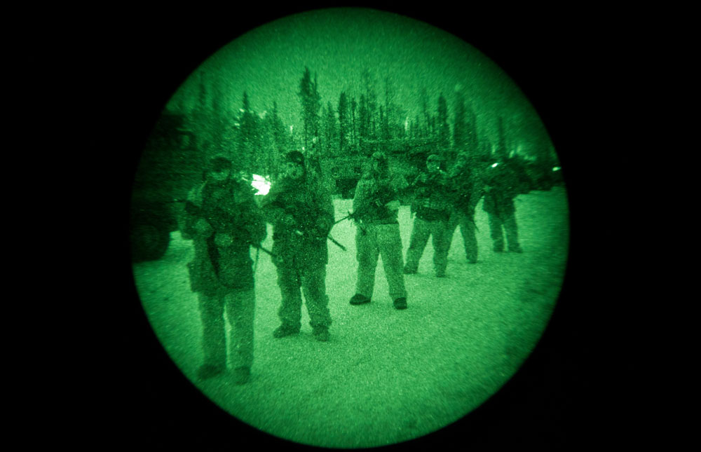 The view through a night vision scope of Canadian solders on night patrol at Forward Operating Base Maiden 1 during Exercise Arctic Ram near Yellowknife on February 13, 2012. Approximately 1,500 Canadian soldiers and Rangers participated in Arctic Ram to re-familiarize the army with a harsh winter environment and to exercise Canada's Arctic sovereignty.