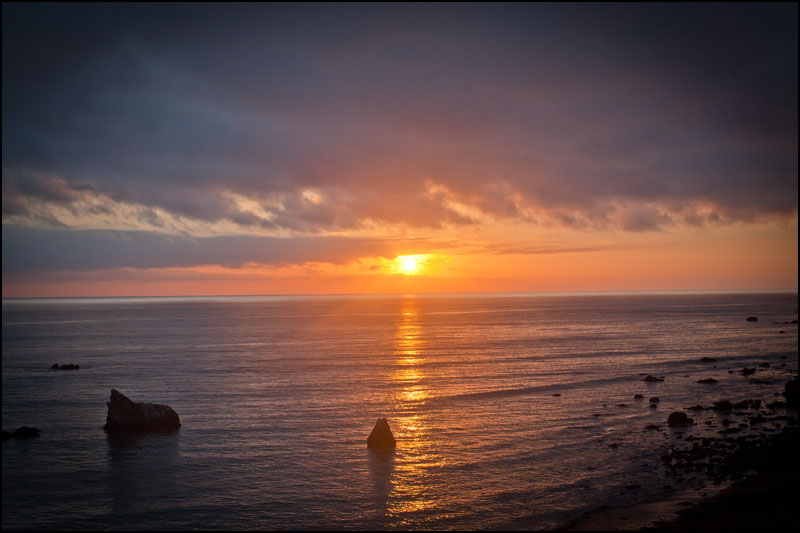 The sun sets on the Pacific Ocean along the west coast Highway-1 in California.