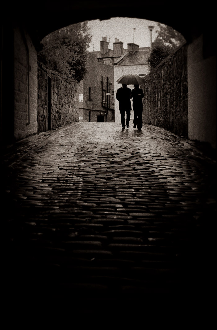 A couple walks down a pathway in Edinburgh, Scotland. 