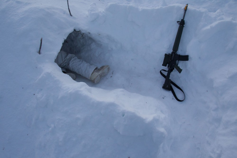 8 Platoon commander Lt. Nick Ethier climbs into a snow cave built during winter survival training with the Canadian Rangers at Forward Operating Base Maiden 1 during Exercise Arctic Ram near Yellowknife on February 14, 2012. Approximately 1,500 Canadian soldiers and Rangers participated in Arctic Ram to re-familiarize the army with a harsh winter environment and to exercise Canada's Arctic sovereignty.