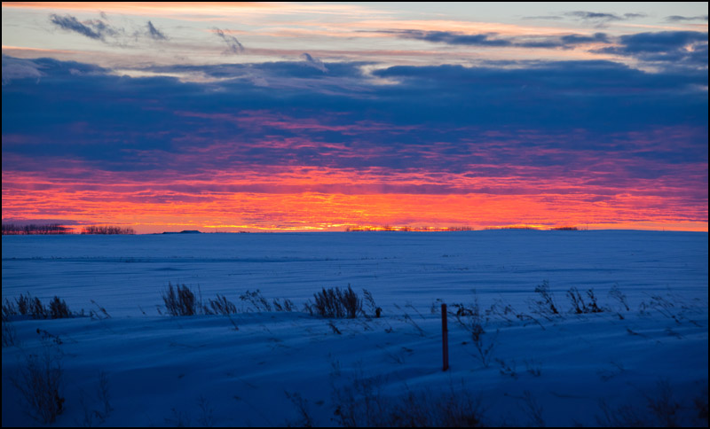 The sun sets on a snowy field along highway 21 near Camrose, Alta. on December 11, 2012. (Ryan Jackson / Edmonton Journal)