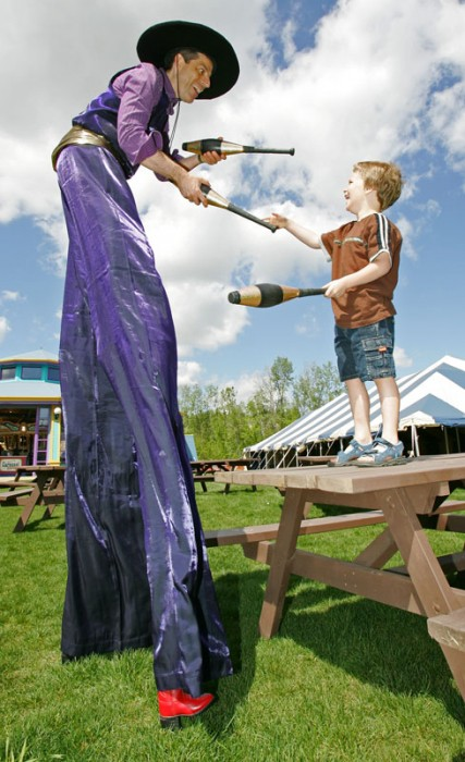 Nikolai teaches six-year-old Damian Volaine to juggle on the midway at Fort Edmonton Park. 2007.