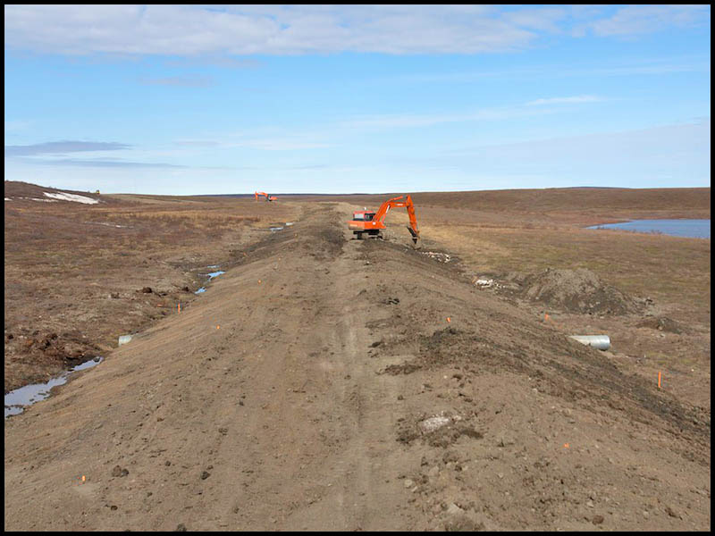 NWT Inuvik to Tuk FP story -  An excavator pushes mounds of earth during the first phase of construction of the Inuvik to Tuktoyaktuk highway. Tuktoyaktuk, NWT. Photo: Ryan Jackson. June 10, 2013. Financial Post