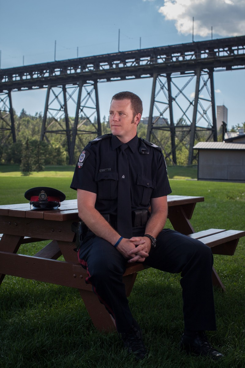 Acting Sgt. Chris Hunter started studying ways to improve safety after responding to numerous calls on the High Level Bridge related to suicide. Hunter poses for a photo in Kinsmen Park in Edmonton on July 28, 2014. The High Level Bridge is considered by some to be a magnet for suicide in Edmonton and the city is investigating measures to reduce the number of people who jump to their deaths. (Photo by Ryan Jackson / Edmonton Journal)
