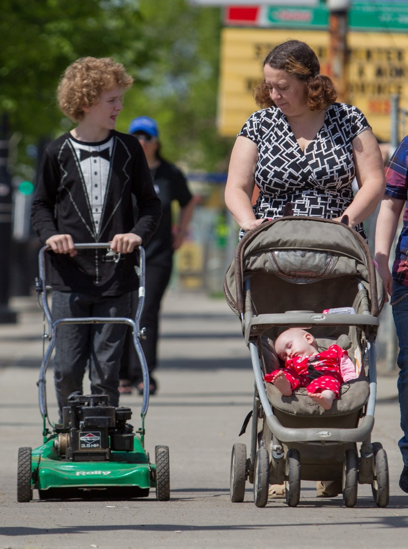 12-year-old Mikhail Kent pushes his new lawnmower 'Betsy' alongside his mother Rhonda Rowsell and 10-month-old niece Rhiannon Rowsell on 118 Ave. near 84 St. in Edmonton on June 3, 2014.  Kent was headed home to mow his mother's lawn.  (Photo by Ryan Jackson / Edmonton Journal)