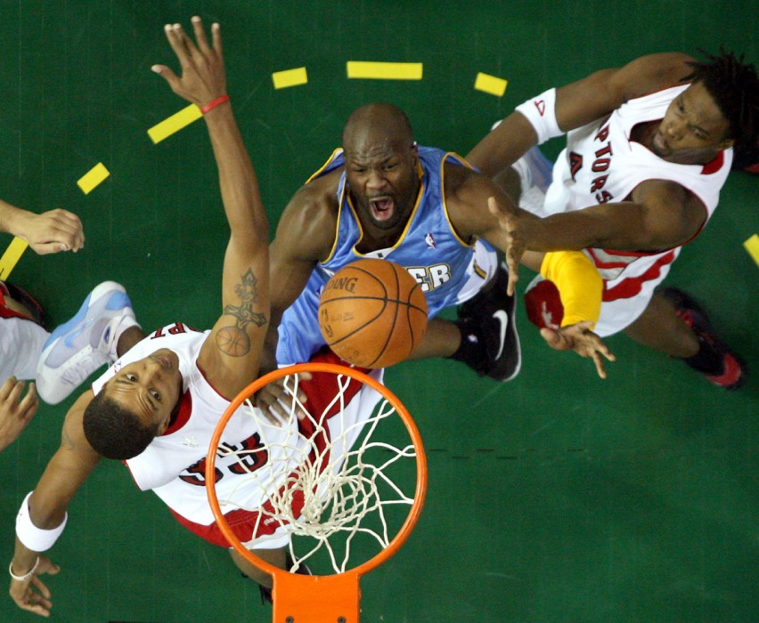 Denver Nuggets' Ruben Patterson grunts as the ball goes in the net despite Toronto Raptors' Jamario Moon and Chris Bosh during first half NBA preseason action at Rexall Place in Edmonton, AB on October 21, 2008.